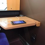 1Aの座席のテーブルと iPhone 充電中( ̄^ ̄)ゞ